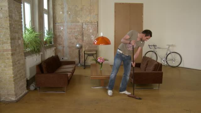 ws man sweeping floor in apartment living room / berlin, germany - sweeping stock videos & royalty-free footage