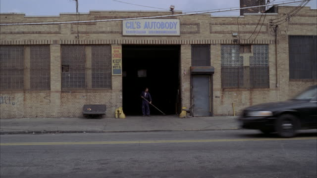 WS Man sweeping in front of autobody repair shop /