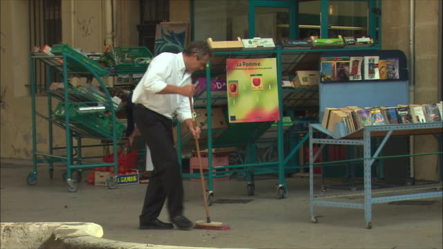 WS Man sweeping in front of shop / Aix-en-Provence, Provence, France
