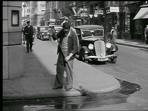 B/W 1936 man sweeping water in street around corner / trafffic + people on sidewalk passing / Paris