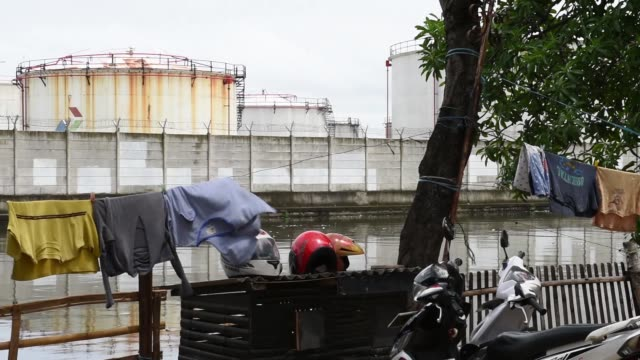 a man sweeps a fishing net through a canal across from fuel storage tanks at a pt pertamina facility at tanjung priok port in jakarta indonesia... - 軍用輸送車点の映像素材/bロール