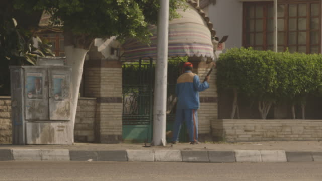 A man sweeps outside the gated entrance to a restaurant in Cairo, Egypt.