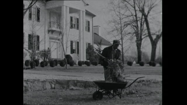 man sweeps up leaves in front of grand house - 1961 stock videos & royalty-free footage
