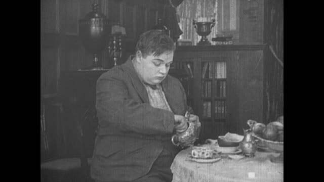 1917 man (fatty arbuckle) sweetens his grapefruit with a large amount of sugar cubes - dice stock videos & royalty-free footage