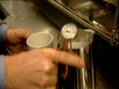 man swills milk in jug before pouring into coffee - milk jug stock videos & royalty-free footage