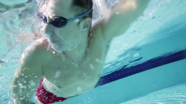 TS Man swimming front crawl in pool, side view shot from underwater