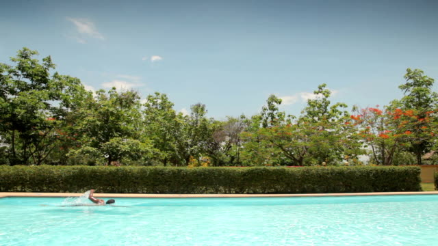 stockvideo's en b-roll-footage met man swimming in a private pool, summer vacation - buitenbad