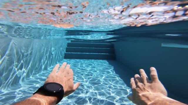 mann schwimmt pov im schwimmbad: sommerentspannung in italien - schwimmen stock-videos und b-roll-filmmaterial