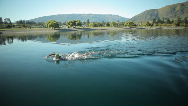 man swimming in lake - diving suit stock videos and b-roll footage