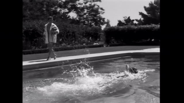 1952 a man swimming in pool meets woman - 1952 stock videos and b-roll footage