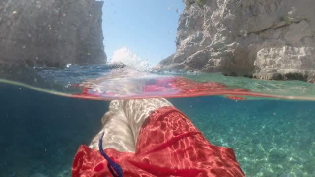 日当たりの良いアドリア海、クロアチアで泳ぐms povの男 - 水中カメラ点の映像素材/bロール