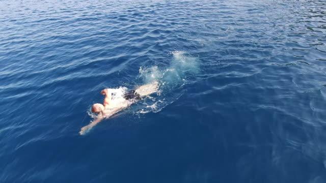 vídeos de stock, filmes e b-roll de homem aérea nadando no mar - swimming