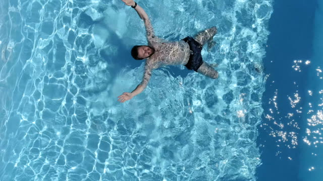 man swimming on his back. aerial view - galleggiare sull'acqua video stock e b–roll