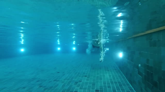 a man swimming underwater in swimming pool, slow motion - freestyle swimming stock videos and b-roll footage