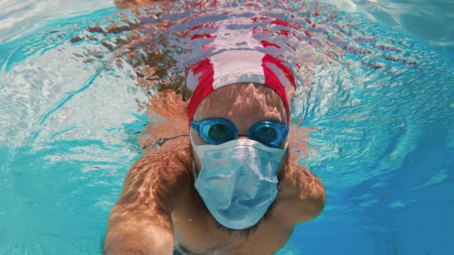 vídeos de stock, filmes e b-roll de homem nadando debaixo d'água com proteção de máscara facial covid em uma piscina: férias seguras - anti higiênico