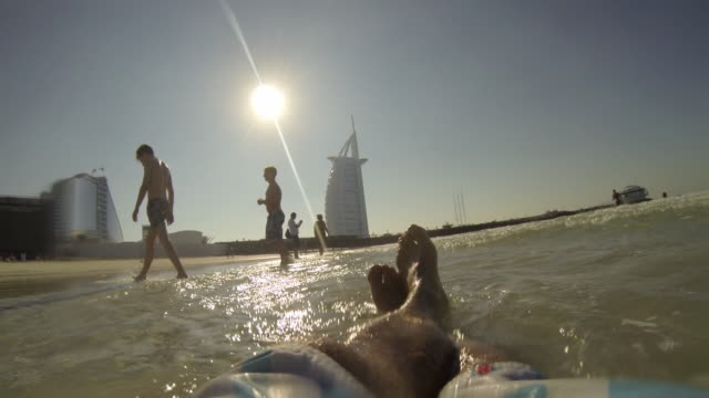 vidéos et rushes de man swims and films selfie at beach near burj al arab -dubai - dubai