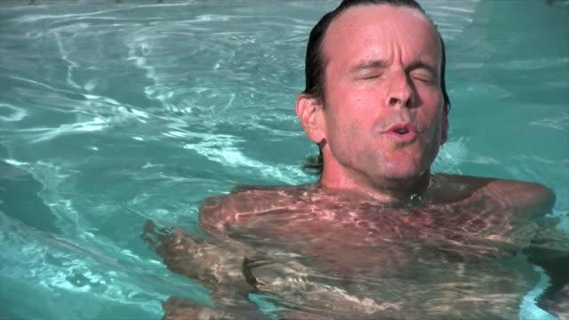 man swims in clear pool - utebassäng bildbanksvideor och videomaterial från bakom kulisserna