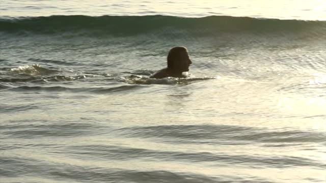 Man swims in open sea, sunrise