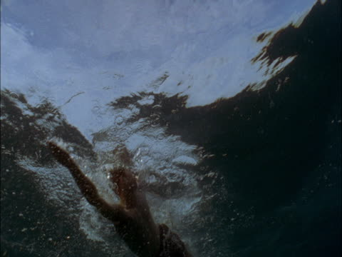 a man swims in sunlit water. - self improvement stock videos & royalty-free footage