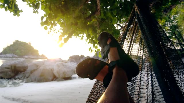 man swinging and resting in a hammock under a tree at sunset sea summer concept - city break stock videos & royalty-free footage