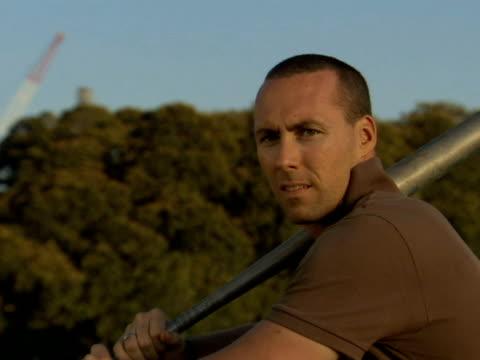 vídeos y material grabado en eventos de stock de cu, man swinging baseball bat and running in park, sydney, australia - barba de tres días