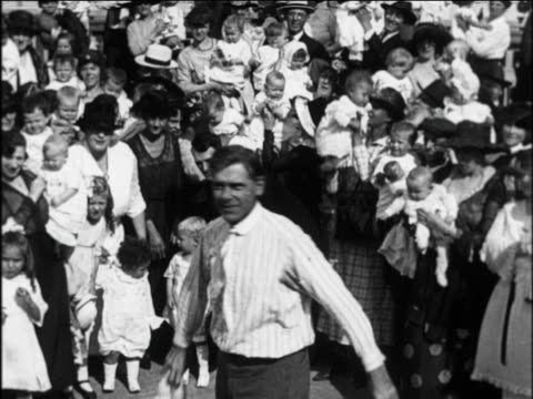 B/W 1924 man swinging crying baby around by feet as crowd watches in background / newsreel