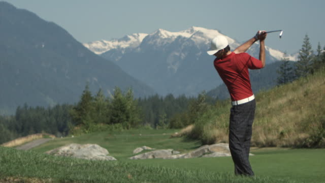 ws slo mo man swinging golf club, mountain in background / squamish, british columbia, canada. - abschlagen stock-videos und b-roll-filmmaterial