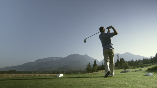 vídeos de stock, filmes e b-roll de ws pan slo mo man swinging golf club / squamish, british columbia, canada. - golfe