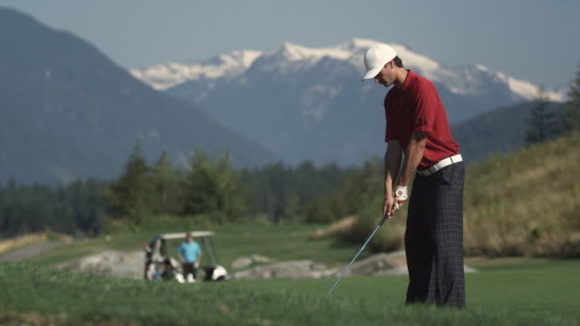 ws man swinging golf club, young man with golf cart in background / squamish, british columbia, canada. - golf glove stock videos and b-roll footage