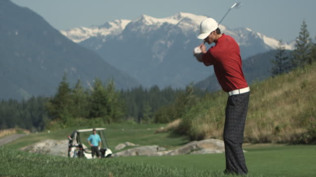 ws slo mo man swinging golf club, young man with golf cart in background / squamish, british columbia, canada. - golf glove stock videos and b-roll footage