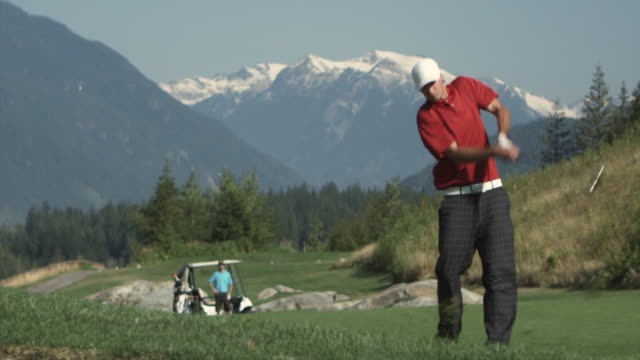ws slo mo man swinging golf club, young man with golf cart in background / squamish, british columbia, canada. - golf swing stock videos & royalty-free footage