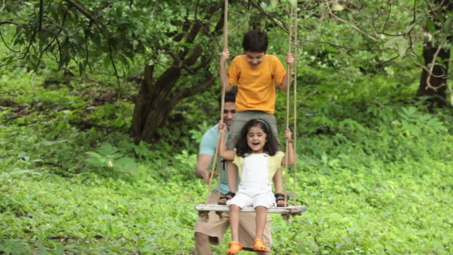 vídeos de stock e filmes b-roll de man swinging his kids in a park, malshej ghat, maharashtra, india - baloiço