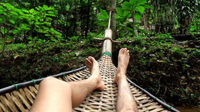 pov 4k, man swinging in hammock in nature forest - reclining stock videos and b-roll footage