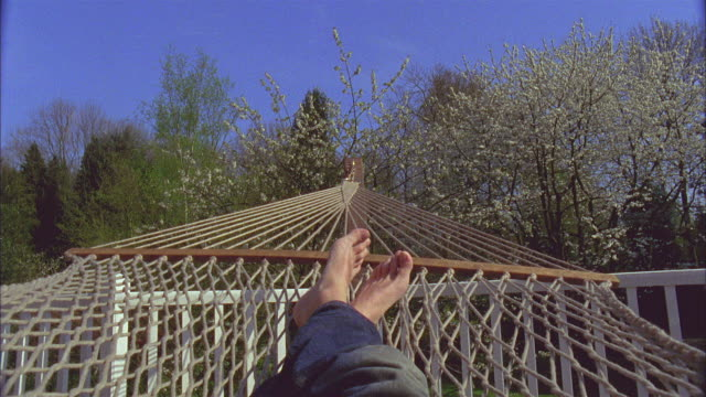 POV, Man swinging in hammock, low section