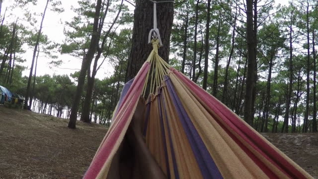 POV Man swinging in hammock