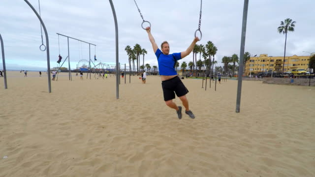 man swinging on gym rings at venice beach los angeles - jungle gym stock videos and b-roll footage