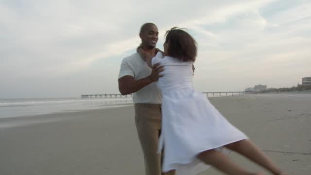 WS ZO SLO MO Man swinging woman around on beach / Jacksonville, Florida, USA