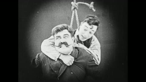 1919 man (buster keaton) swings across a theater on a rope swing, pulls strongman (charles a post) off of the balcony, and a stagehand drops a chest filled with weights onto the strongman, knocking him to the ground unconscious - 1910 1919 stock videos & royalty-free footage