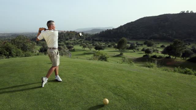 ws man swings at golf ball with driver / palma de mallorca, mallorca, baleares, spain - ゴルフのスウィング点の映像素材/bロール