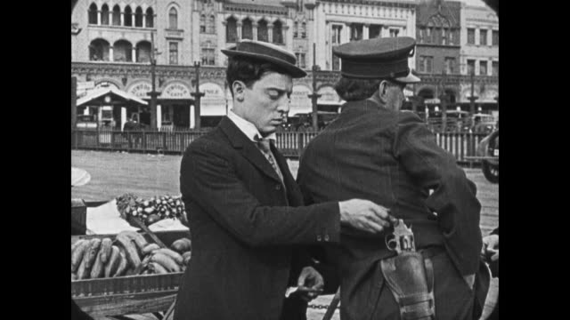 1921 man (buster keaton) swipes cop's gun and replaces it with banana - schurke stock-videos und b-roll-filmmaterial