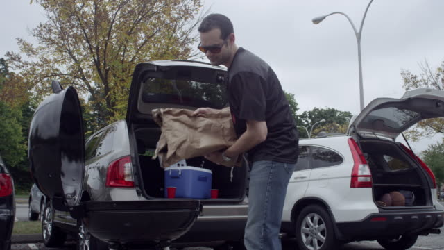 man tailgating in parking lot - cooler container stock videos and b-roll footage