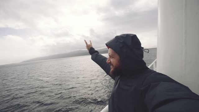 vidéos et rushes de l'homme prend un selfie sur le bateau à voile : vlogging de l'arctique - marin
