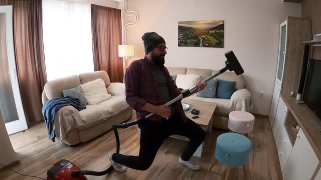 man take a selfie video at home. a happy man dressed in a modern style sings and plays while vacuuming and tidying up the apartment. - hipster culture stock videos & royalty-free footage