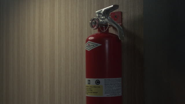 a man takes a fire extinguisher off of a hook on the wall. - fire extinguisher stock videos & royalty-free footage