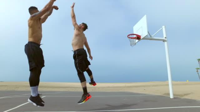 a man takes a jump shot while playing one-on-one basketball hoops on a beach court. - mindre än 10 sekunder bildbanksvideor och videomaterial från bakom kulisserna