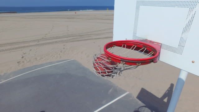 a man takes a jump shot while playing one-on-one basketball hoops on a beach court. - jump shot stock videos and b-roll footage