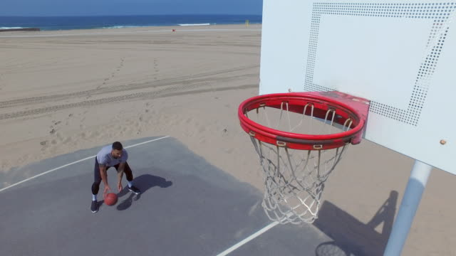 A man takes a layup shot while playing one-on-one basketball hoops on a beach court.