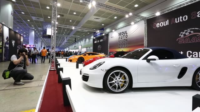 a man takes a photograph of a customized vehicle on display at the seoul auto salon 2013 in seoul south korea on thursday july 11 pull focus... - customised stock videos & royalty-free footage