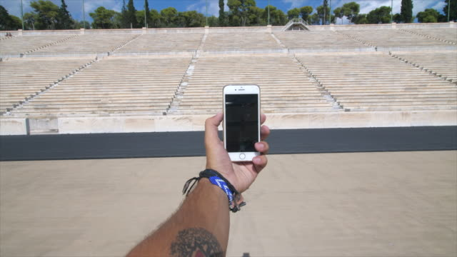 a man takes a picture of a woman tourist sightseeing at the panathenaic stadium in athens, greece. - panathinaiko stadium stock videos & royalty-free footage