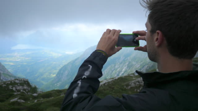 a man takes a picture of the view while hiking in the mountains. - slow motion - risk stock videos & royalty-free footage